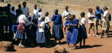 School children in Tanzania share their Scriptures with friends after a distribution.