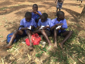 A group of boys explore their New Testaments after receiving them from Gideons during the 2016 Uganda ISB.