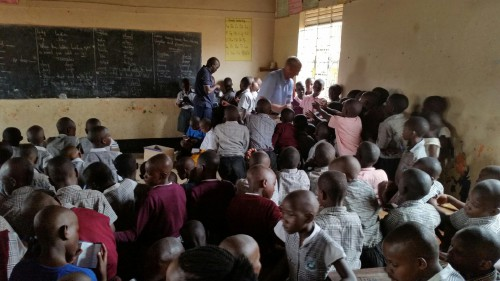 Students in a Uganda school classroom line up to get their Scriptures from Gideons.